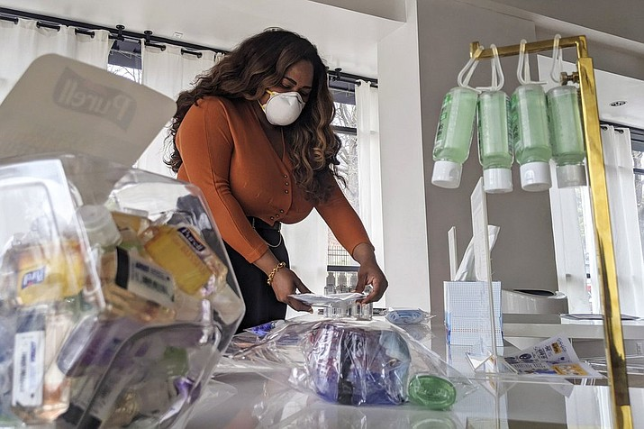 Adilisha Patrom, owner of a co-working and event space next to Gallaudet University, organizes face masks, hand sanitizer and other supplies inside her pop up shop on Thursday, March 5, 2020, in Washington. Inside her storefront, she displays different face mask models and hand sanitizer bottles alongside information from the Centers for Disease Control and Prevention. (AP Photo/Nathan Ellgren)