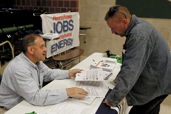 In this Nov. 2, 2017, photo, a recruiter in the shale gas industry, left, speaks with an attendee of a job fair in Cheswick, Pa. Hiring in the United States jumped in February 2020 as employers added a robust 273,000 jobs, evidence that the economy was in strong shape before the coronavirus began to sweep through the nation.(Keith Srakocic/AP, file)