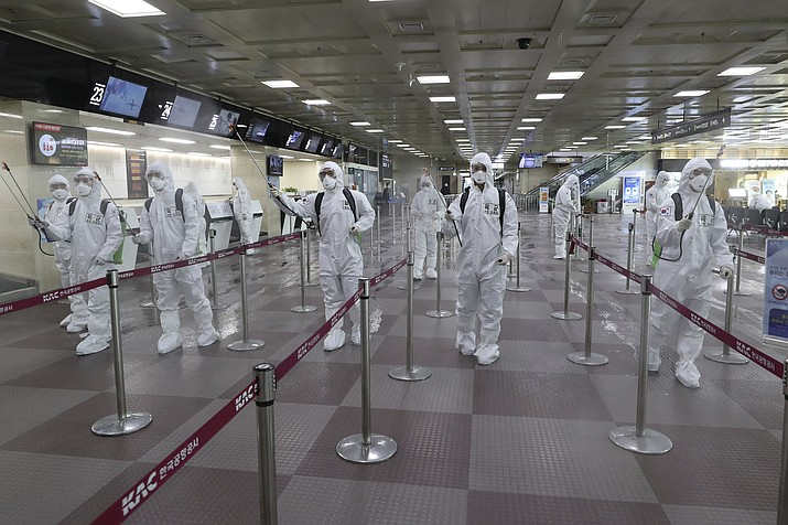 In this March 6, 2020 photo, South Korean army soldiers wearing protective suits spray disinfectant to prevent the spread of the new coronavirus at Daegu International Airport in Daegu, South Korea. As cases of the coronavirus surge in Italy, Iran, South Korea, the U.S. and elsewhere, many scientists say it's plain that the world is in the grips of a pandemic — a serious global outbreak. (Kim Joo-sung/Yonhap via AP)