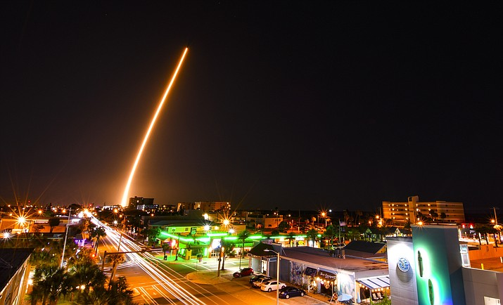 In a time exposure, a SpaceX Falcon is launched from Cape Canaveral, Fla., Friday night, March 6, 2020, with a load of supplies for the International Space Station. Cocoa Beach, Fla., is in the foreground. (Malcolm Denemark/Florida Today via AP)