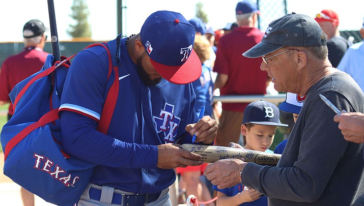 Signing autographs, as Texas Rangers outfielder Miguel Aparicio is doing for a fan in Surprise, has given some players a moment of pause as concerns about the Coronavirus escalate. (Photo by Reno Del Toro/Cronkite News)