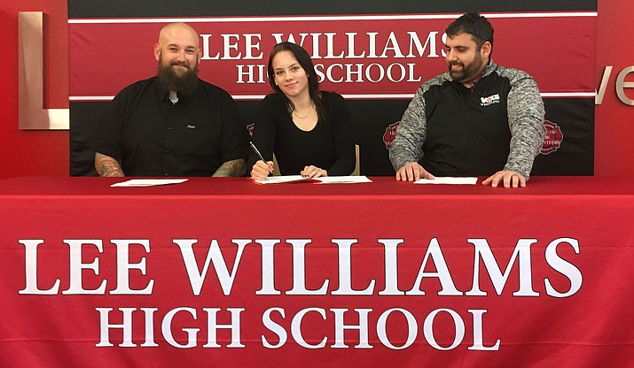Lee Williams senior Stephanie Broadbent is joined by her dad, left, and Vols head coach Dan Ondrejka as she signs her letter of intent to wrestle at Dixie State University. (Photo by Beau Bearden/Kingman Miner)