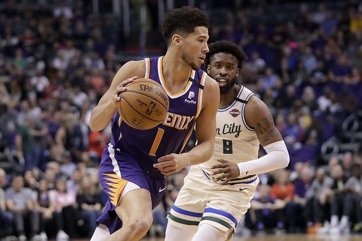 Phoenix Suns guard Devin Booker (1) drives as Milwaukee Bucks guard Wesley Matthews defends during the first half of an NBA basketball game Sunday, March 8, 2020, in Phoenix. (Matt York/AP)