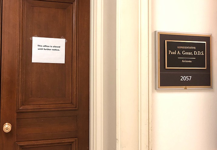 """The Capitol Hill office door of Rep. Paul Gosar, R-Ariz., has a sign that reads, """"This office is closed until futher notice,"""" shown Monday, March 9, 2020 on Capitol Hill in Washington. On Sunday, Sen. Ted Cruz, R-Texas, and Gosar said they're isolating themselves after determining they had contact with a person at a Maryland political conference who got COVID-19. (Padmananda Rama/Associated Press)"""
