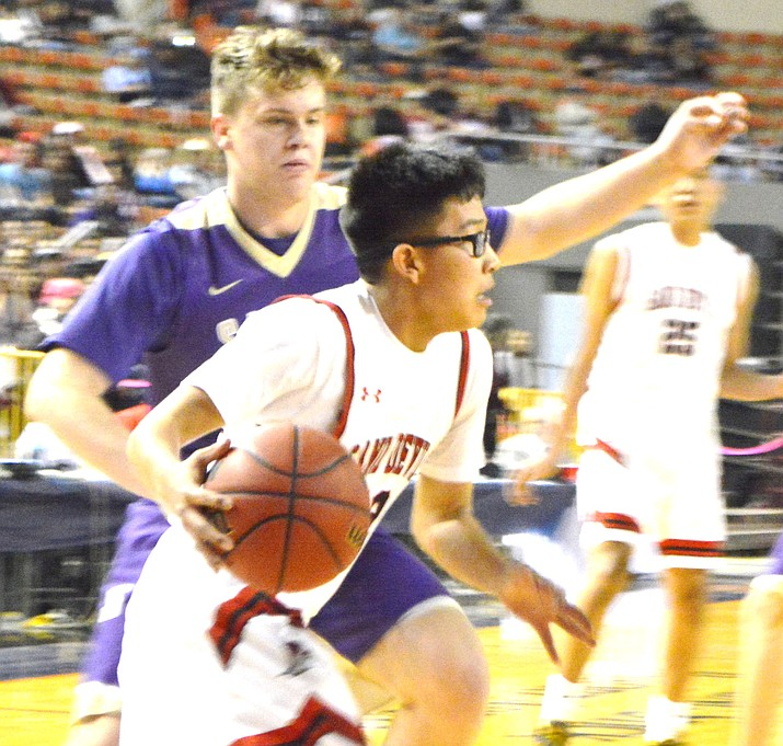 Page Sand Devils' Robert Smith (1) looks for an open teammate, with Sabino's Gabe Gomez (5) defending, during the Arizona State 3A Boys state tournament semifinals game at the Veterans Memorial Coliseum Feb. 28. Sabino won by a score of 53 to 50. (Anton Wero/NHO)