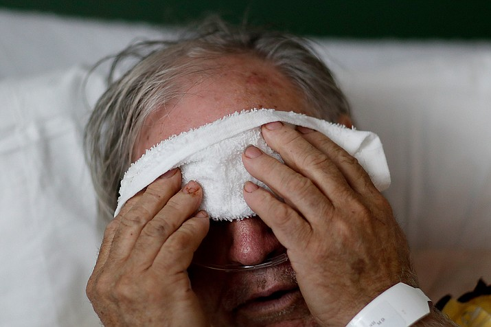 In this Friday, Feb. 9, 2018 photo, a 73-year-old man places a cold compress on his forehead while battling the flu at a hospital in Georgia. Doctors can test for the flu and get results within a day, but coronavirus testing as of March 2020 is still limited in the United States by availability. (David Goldman/AP)