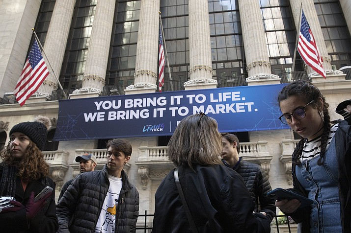 In this Monday, March 9, 2020 photo, people stop to look at the New York Stock Exchange. Stocks are opening sharply lower on Wall Street Wednesday as fears of economic fallout from the coronavirus outbreak grip markets again. (Mark Lennihan/AP, File)