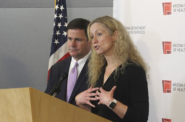 Arizona Department of Health Services Director Dr. Cara Christ, at podium, explains the effects of a public health emergency declaration ordered by Gov. Doug Ducey, left, at a news conference in Phoenix Wednesday, March 11, 2020. (AP Photo/Bob Christie)