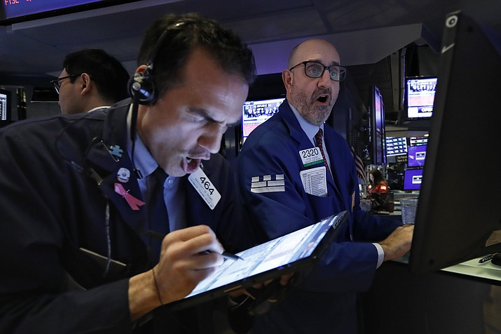 Trader Gregory Rowe, left, and specialist Peter Giacchi work on the floor of the New York Stock Exchange, Thursday, March 12, 2020. Stocks are sharply lower after resuming trading as traders fear that not enough is being done to contain the economic damage from the coronavirus pandemic. (Richard Drew/AP)