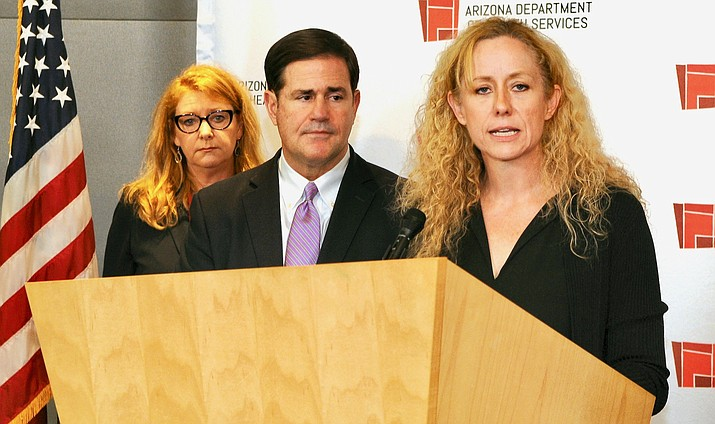 State Health Director Cara Christ explains Wednesday some of what will change now that Gov. Doug Ducey has declare a public health emergency. With them is Dana Kennedy, state director of AARP. (Capitol Media Services photo by Howard Fischer)