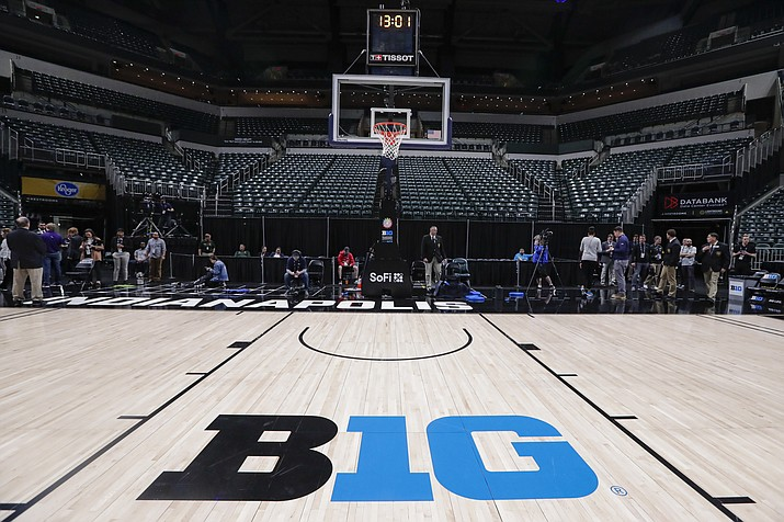 The seating area at Bankers Life Fieldhouse is empty as media and staff mill about, Thursday, March 12, 2020, in Indianapolis, after the Big Ten Conference announced that remainder of the men's NCAA college basketball games tournament was cancelled. (Michael Conroy/AP)