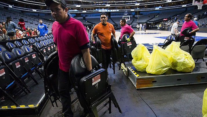 "Crews remove chairs from the court after the Dallas Mavericks defeated the Denver Nuggets  on Wednesday. The NBA has suspended its season ""until further notice."" (Photo courtesy of Ashley Landis/The Dallas Morning News via AP)"