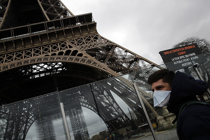 A man wearing a mask walks pasts the Eiffel tower closed after the French government banned all gatherings of over 100 people to limit the spread of the virus COVID-19, in Paris, March 14. For most people, the new coronavirus causes only mild or moderate symptoms. For some it can cause more severe illness, especially in older adults and people with existing health problems. (AP Photo/Christophe Ena)