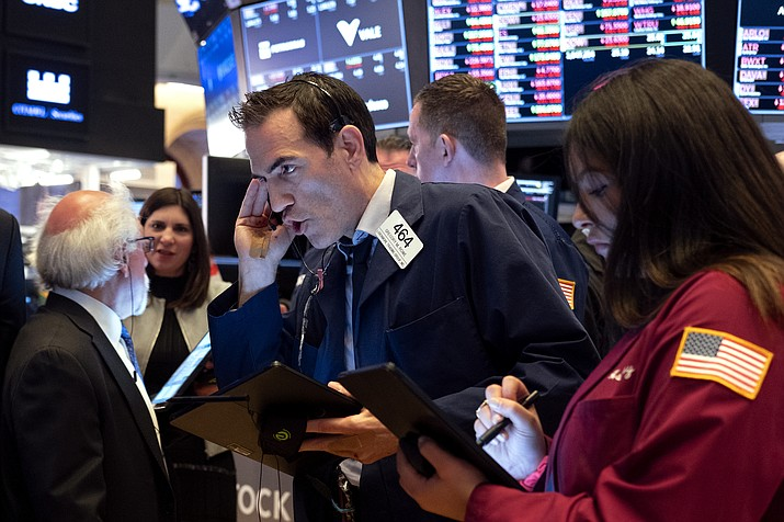 Trader Gregory Rowe, center, and others work on the floor of the New York Stock Exchange Monday, March 16, 2020. (AP Photo/Craig Ruttle)