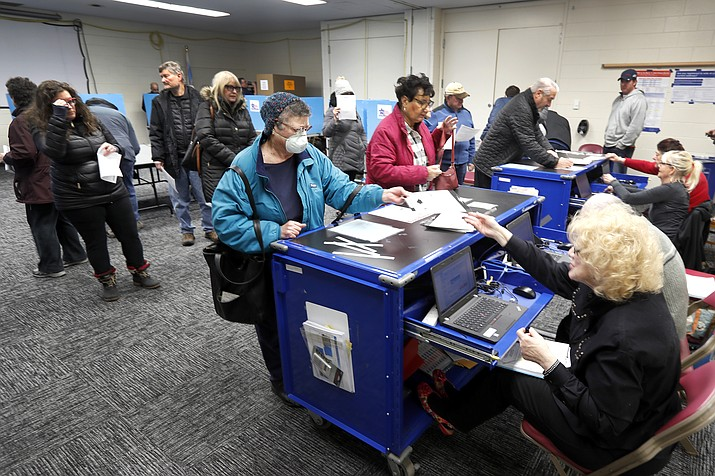 Chicago residents line up for early voting at the Roden Library Monday, March 16, 2020, in Chicago. (Charles Rex Arbogast/AP)