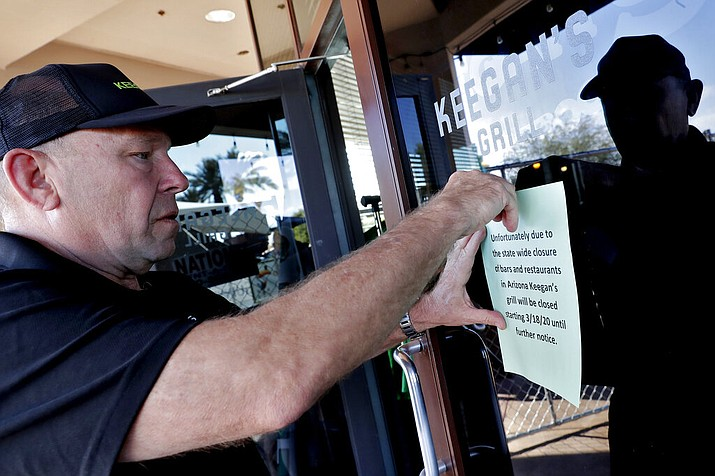 Owner Steve Johnson attaches a notice on the door of Keegan's Grill Tuesday, March 17, 2020, in Phoenix notifying guests his restaurant will closing in compliance with the state of emergency issued by the city of Phoenix earlier in the day that restaurants only serve take-out. Phoenix, Tucson and Flagstaff have ordered bars, gyms and other indoor facilities to close immediately and restaurants to offer to-go service only in an effort to slow the spread of the coronavirus. (AP Photo/Matt York)