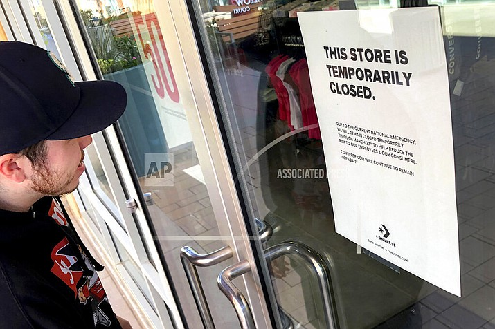 An employee enters a closed Converse shoe store Monday, March 15, 2020, in Phoenix. Nike, which owns Converse, is closing all of its stores in the U.S., along with other parts of the world, to try to curb the spread of COVID-19 coronavirus. According to the World Health Organization, most people recover in about two to six weeks, depending on the severity of the illness. (AP Photo/Matt York)