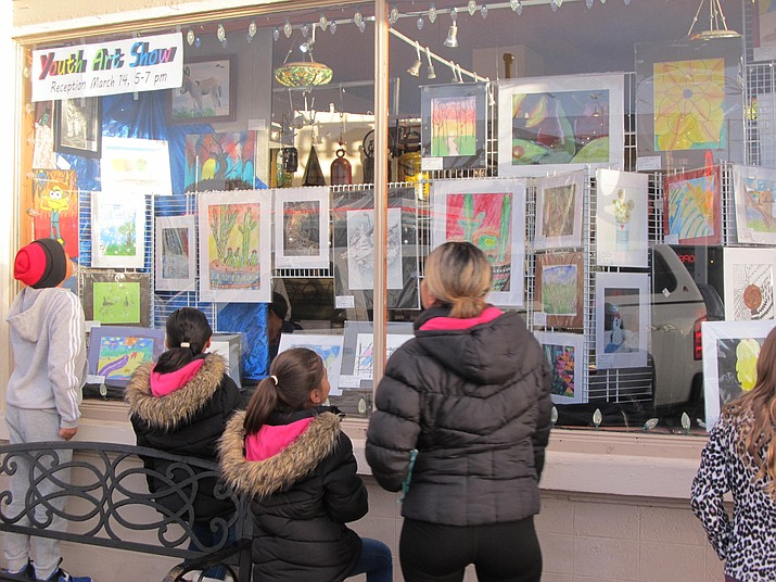 The Lara family admires the store front display at The Gallery in Williams celebrating Youth Art Month. (B. Garibay/WGCN)