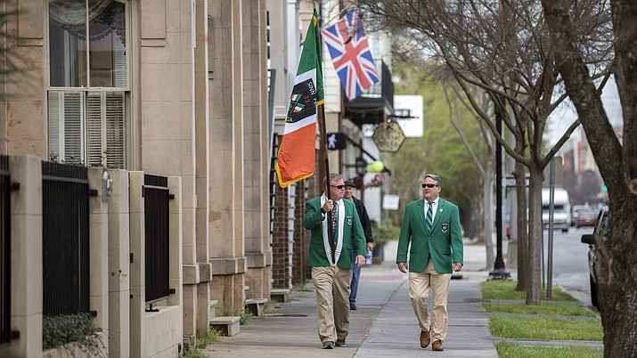 Sinn Fein Society members Bill Bradley, left, and John Lowenthal, right, walk the sidewalk of the St. Patrick's Day parade route in downtown Savannah, Ga., Tuesday, March 17, 2020. Last week, Savannah's mayor announced the city's 196-year-old St. Patrick's Day parade was called off due to coronavirus concerns. (Stephen B. Morton/AP)