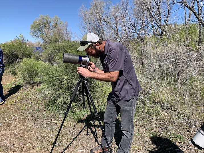 Kenneth Jacobson, a bald eagle management coordinator with the Arizona Game and Fish Department, trains a telescope on a bald eagle nest. (Photo by Isabella Hulsizer/Cronkite News)