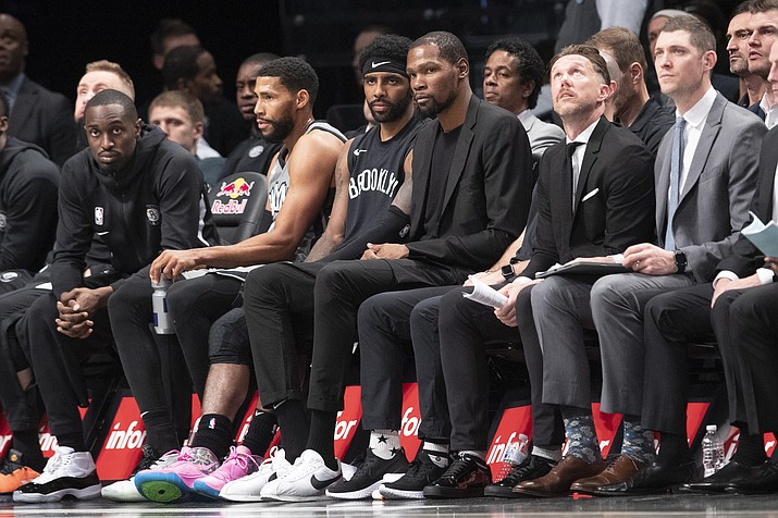 Brooklyn Nets guard Kyrie Irving, center left, and forward Kevin Durant, center right, watch the action from the bench a game against the New Orleans Pelicans, Monday, Nov. 4, 2019, in New York. (Mary Altaffer/AP, file)