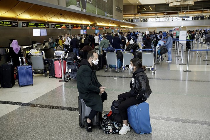 In this Saturday, March 14, 2020 file photo, travelers wait to check in their luggage at the Los Angeles International Airport. The coronavirus pandemic that's caused many Americans to avoid airports has others booking spur-of-the moment trips at dirt-cheap ticket prices. (AP Photo/Marcio Jose Sanchez)