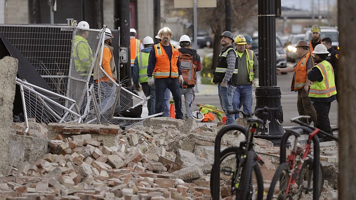 Construction workers looks at the rubble from a building after an earthquake Wednesday, March 18, 2020, in Salt Lake City. A 5.7-magnitude earthquake has shaken the city and many of its suburbs. The quake sent panicked residents running to the streets, knocked out power to tens of thousands of homes and closed the city's airport and its light rail system.  (Rick Bowmer/AP)