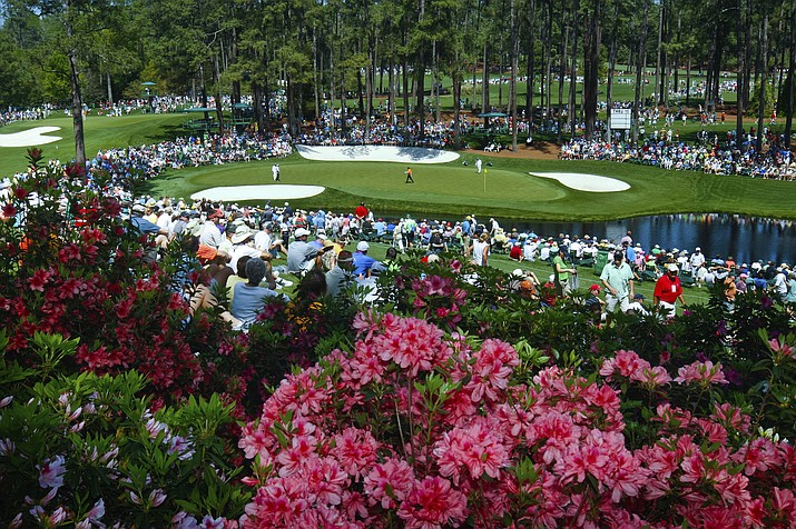 In this April 4, 2011, photo, golf fans watch practice on the par three 16th hole during a practice round for the Masters at Augusta National Golf Club in Augusta, Ga. (Tim Dominick/The State via AP, file)