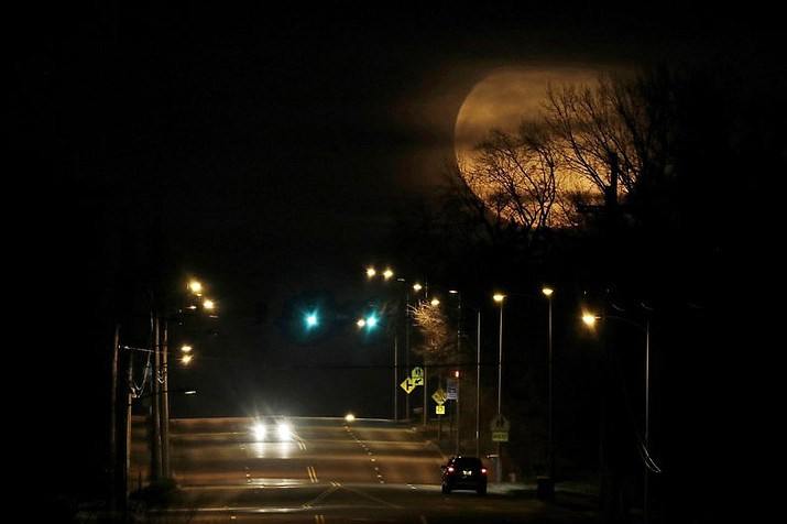 In this March 10, 2020, file photo, vehicles are dwarfed as the nearly full moon rises in the distance in Shawnee, Kan. The planets and our moon are providing some early morning entertainment. Mars, Jupiter, Saturn and a crescent moon will be clustered together in the southeastern sky just before daybreak. Mercury will peek above the horizon. (AP Photo/Charlie Riedel)