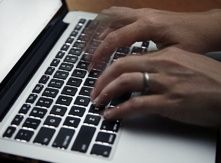 This June 19, 2017 file photo shows a person working on a laptop in North Andover, Mass. The U.S. internet won't get overloaded by spikes in traffic from the millions of Americans now working from home to discourage the spread of the new coronavirus, experts say. But connections could stumble for many if too many family members try to videoconference at the same time. (AP Photo/Elise Amendola)