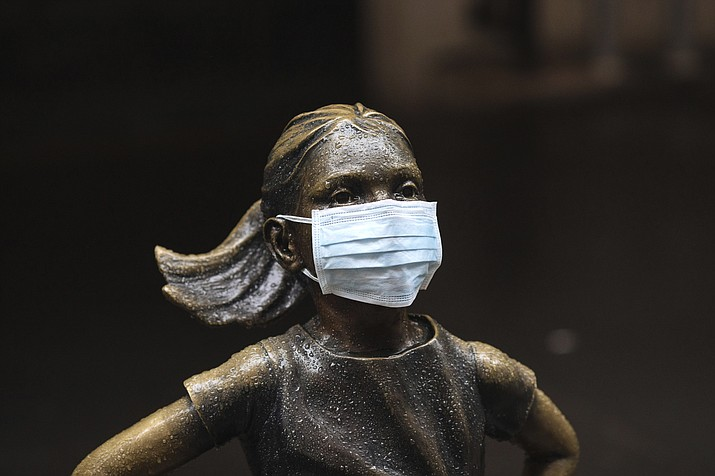"""A surgical mask is placed on The """"Fearless Girl"""" statue outside the New York Stock Exchange on Thursday, March 19, 2020, in New York. Stocks are swinging between gains and losses in early trading on Wall Street Thursday, but the moves are more subdued than the wild jabs that have dominated recent weeks. (Kevin Hagen/AP)"""