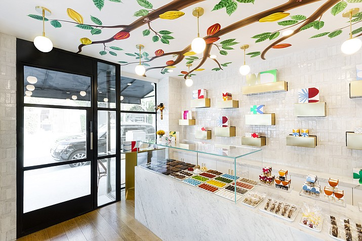 This 2019 photo shows the inside of andSons Chocolatiers in Beverly Hills, Calif., which was designed by Lauren Buxbaum Gordon and Nate Berkus. Homeowners who want to take decorating inspiration from their favorite public places should consider what specific elements they like best, such as appealing lighting. Inside andSons, ample natural light is paired with soft pendant lighting to create a light-filled, inviting space. (Christopher Dibble/Lauren Buxbaum Gordon via AP)