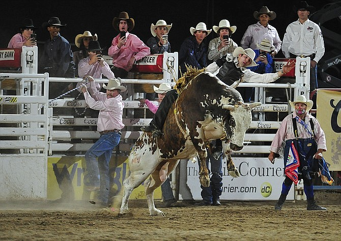 JC Mortensen on Bank Roll in the bull riding during the second performance of the Prescott Frontier Days Rodeo Tuesday July 2, 2019. The 18-year-old Mortensen is in good standing to compete in the Arizona High School State Finals Rodeo in Prescott from June 3-7. (Les Stukenberg/Courier, file)