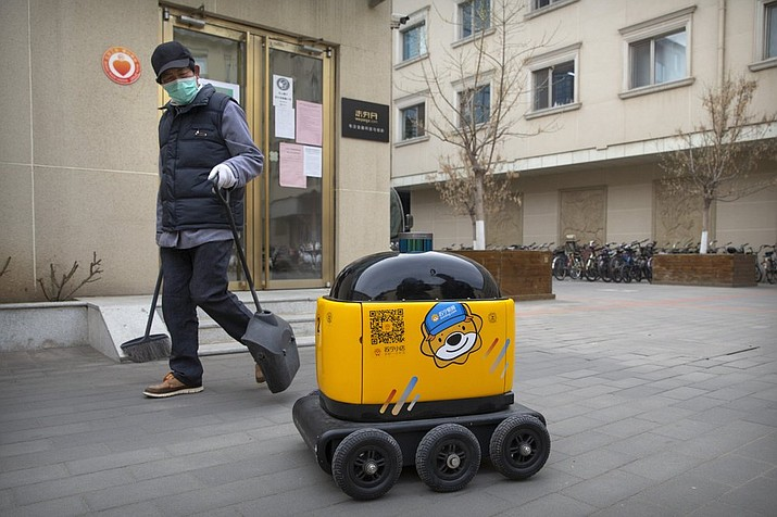 In this March 18, 2020, photo, a maintenance worker looks at a robot outside the offices of ZhenRobotics in Beijing. While other industries struggle, one robot maker says China's virus outbreak is boosting demand for his knee-high, bright yellow robots to deliver groceries and patrol malls for shoppers who fail to wear masks. (AP Photo/Mark Schiefelbein)