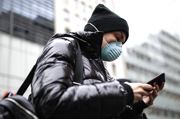 A pedestrian uses her phone while wearing a face mask in Herald Square, March 12, in New York. (AP Photo/John Minchillo)