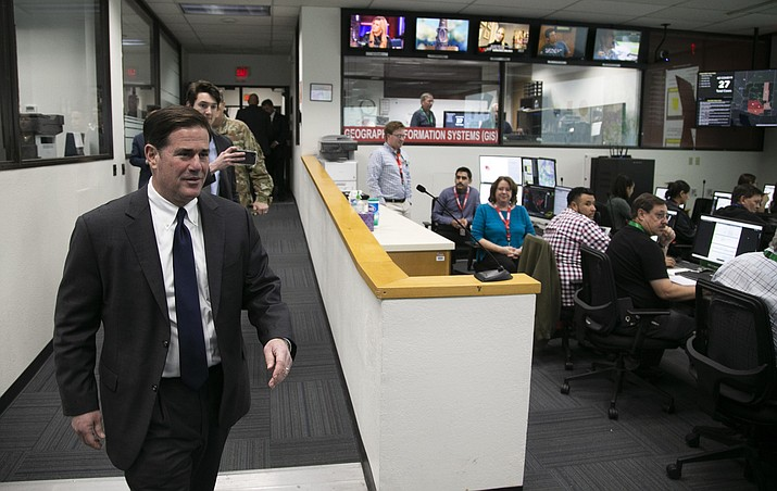 Gov. Doug Ducey walks into the State of Arizona Department of Emergency and Military Affairs operations center as members of DEMA work while responding to the coronavirus pandemic, in the DEMA operations center at the Arizona National Guard Papago Park Military Reservation in Phoenix, Wednesday, March 18, 2020. (David Wallace/The Arizona Republic via AP, Pool)