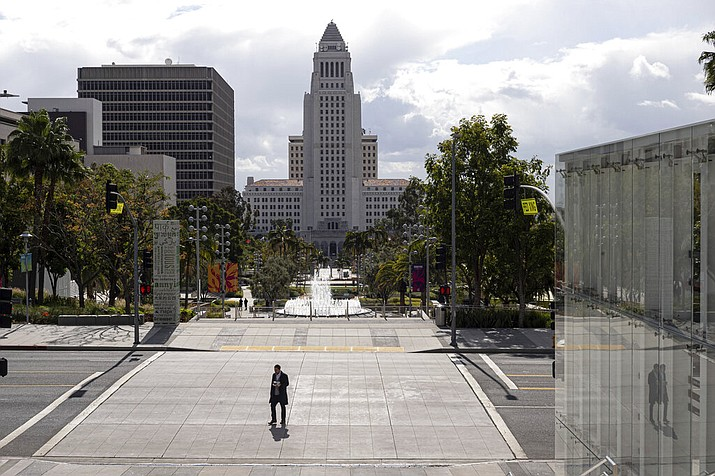 A lone pedestrian crosses Grand Avenue with Los Angeles city hall as a backdrop in downtown Los Angeles on Thursday, March 19, 2020. The coronavirus has closed restaurants, stores, theaters and many commuters are now working from home. (David Crane/The Orange County Register/SCNG via AP)