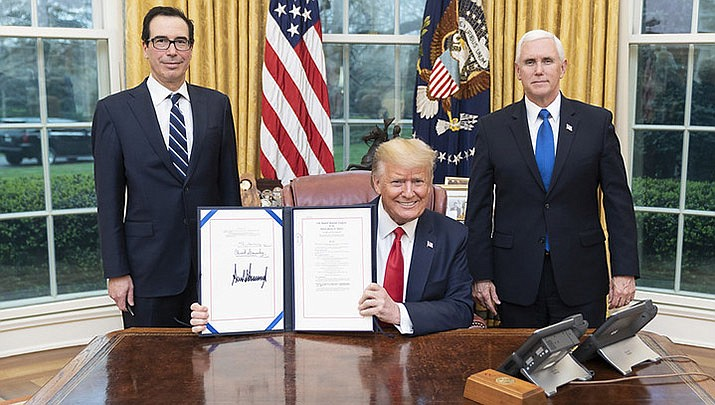 U.S. Treasury Secretary Steve Mnuchin, left, and U.S. Vice President Mike Pence, right, pose with President Donald Trump after he signed a stimulus bill. Negotiations are now underway in Congress for a larger, $1 trillion economic rescue package. (Official White House photo/public domain)
