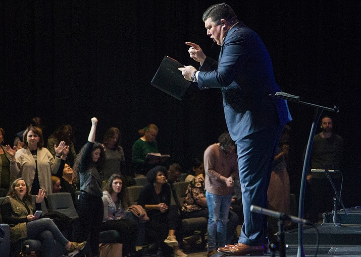 In this Sunday, March 15, 2020 photo, Redemption to the Nations church Lead Pastor Kevin Wallace preaches to his congregation about trusting God to help them get through the COVID-19 coronavirus threat in Chattanooga, Tenn. (Chattanooga Times Free Press/Troy Stolt via AP)