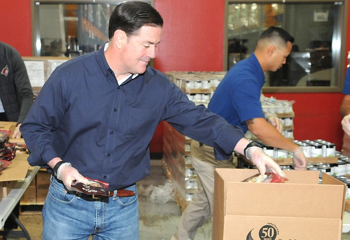 Gov. Doug Ducey helps load food boxes Friday at St. Mary's Food Bank in Phoenix. (Capitol Media Services photo by Howard Fischer)