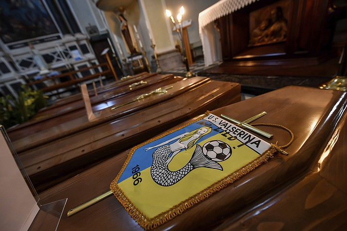 Coffins, one of them with the pennant of the local soccer team, wait to be transported to cemetery, in the church of Serina, near Bergamo, Northern Italy, Saturday, March 21, 2020. Italy's tally of coronavirus cases and deaths keeps rising, with new day-to-day highs: 793 dead and 6,557 new cases. For most people, the new coronavirus causes only mild or moderate symptoms. For some it can cause more severe illness. (Claudio Furlan/LaPresse via AP)