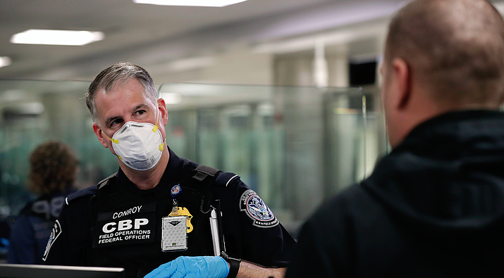 A Customs and Border Protection officer talks with an international traveler this week at Dulles International Airport in Northern Virginia. CBP officers have recently started wearing personal protective equipment, like masks and gloves, in response to the coronavirus. (Photo by Glenn Fawcett/U.S. Customs and Border Protection)