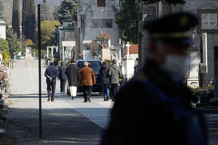 Relatives walk behind a hearse carrying a coffin inside the Monumentale cemetery, in Bergamo, the heart of the hardest-hit province in Italy's hardest-hit region of Lombardy, Italy. (Luca Bruno/AP)