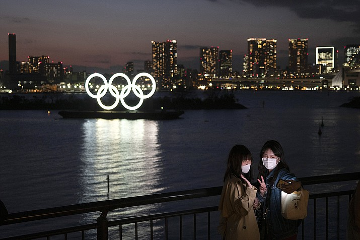Two women take a selfie with the Olympic rings in the background in the Odaiba section of Tokyo, Thursday, March 12, 2020. Doping testers around the sporting world are trying to avoid infecting themselves or athletes during the global virus outbreak, and that's not easy when collecting samples means getting very close to sports stars. (Jae C. Hong/AP)