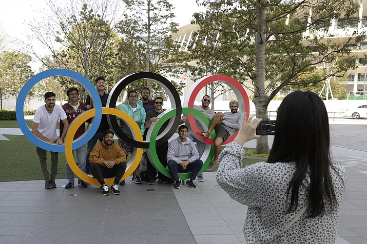 A group of students from Uruguay pose for a souvenir picture on the Olympic Rings set outside the Olympic Stadium in Tokyo, Saturday, March 21, 2020. The Olympic flame from Greece arrived in Japan Friday, even as the opening of the the Tokyo Games in four months is in doubt with more voices suggesting the games should to be postponed or canceled because of the worldwide virus pandemic. (Gregorio Borgia/AP)
