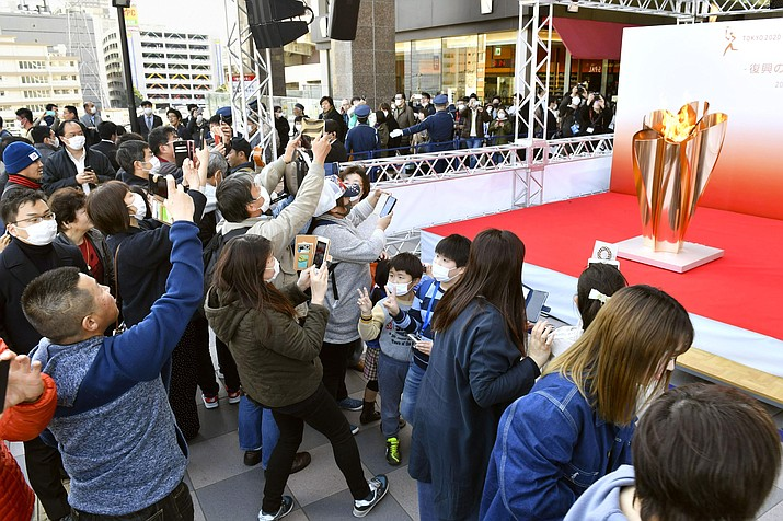 People gather to take a look at Olympic flame on display in Sendai, Miyagi prefecture, north of Tokyo Saturday, March 21, 2020. The Olympic flame from Greece arrived in Japan Friday, and the flame will be on public display in the some areas affected by the 2011 earthquake and tsunami ahead of the Olympic torch relay. (Kyodo News via AP)