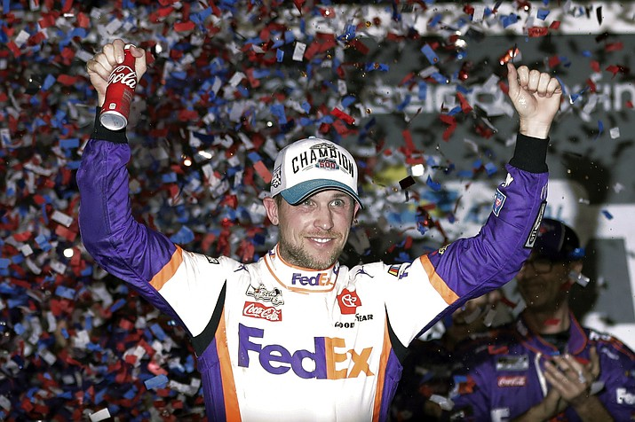 In this Monday, Feb. 17, 2020 file photo,Denny Hamlin celebrates in Victory Lane after winning the NASCAR Daytona 500 auto race at Daytona International Speedway in Daytona Beach, Fla. NASCAR eased off the brake in the real sports world brought to a sudden halt by the coronavirus and introduced the country to iRacing with some of the sports biggest stars. Hamlin, the three-time Daytona 500 winner, beat Dale Earnhardt Jr. off the final corner Sunday, March 22, 2020 at virtual Homestead-Miami Speedway to win the bizarre spectacle. (John Raoux, AP File)