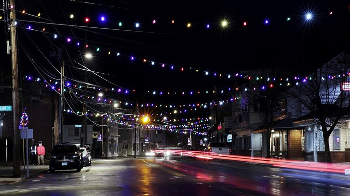 In this March 19, 2020, photo, car tail lights streak under Christmas lights recently turned back on in Farmington, N.H. As the coronavirus spreads, holiday lights are going back up to provide a bit of emotional and actual brightness. (AP Photo/Charles Krupa)