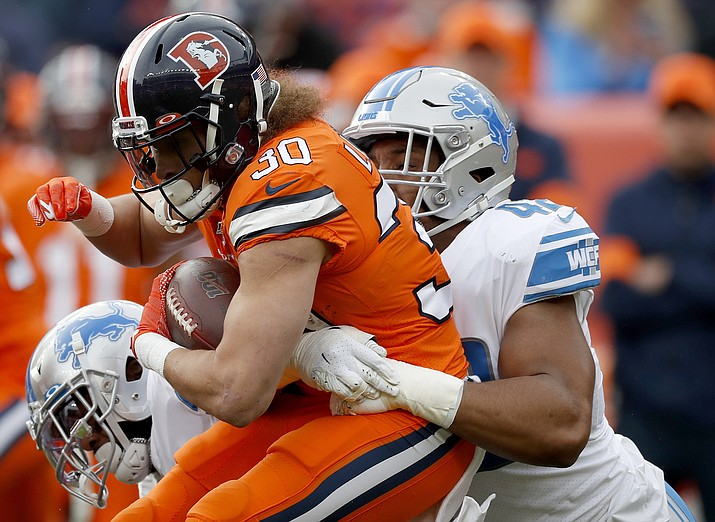 In this Dec. 22, 2019, file photo, Denver Broncos running back Phillip Lindsay (30) is tackled by Detroit Lions outside linebacker Devon Kennard during the first half of an NFL football game in Denver. Arizona native Kennard is ready to aid the Cardinals' defensive rebuild. The edge rusher had seven sacks in each of the past two seasons with the Lions and agreed to a three-year deal with the Cardinals on March 15, 2020. (David Zalubowski, AP File)