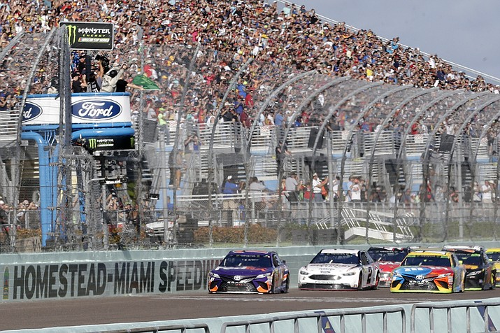In this Nov. 18, 2018, file photo, Denny Hamlin, left, leads the pack at the start of the NASCAR Cup Series championship auto race at Homestead-Miami Speedway, in Homestead, Fla. NASCAR is suspended until at least May 9 because of the COVID-19 pandemic so the series and iRacing created an invitational to give its drivers something to do. Fox Sports 1 jumped on board, 35 drivers agreed to participate and suddenly there was live sports programming on Sunday. (Lynne Sladky, AP File)